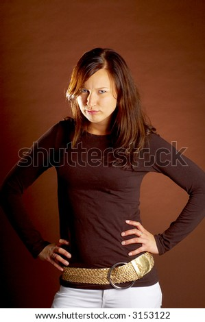 Young woman posing on a braun background with some attitude - stock photo