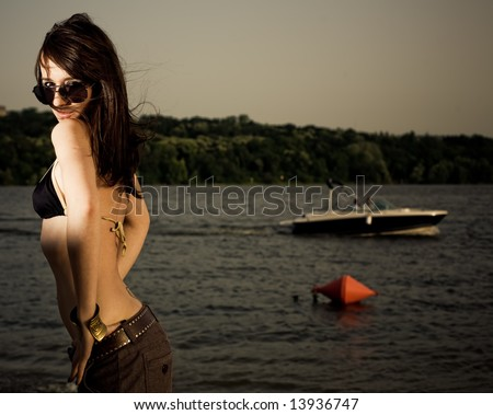 Young woman posing on beach near water in bikini with large copyspace and yacht in background