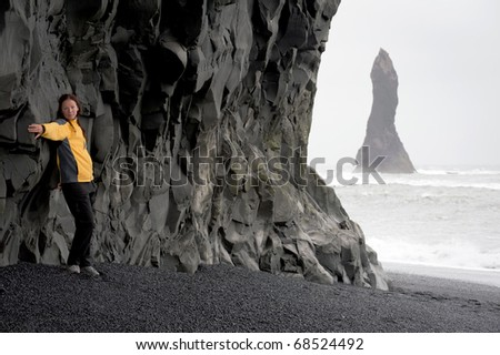 young woman posing on the Black sand beach near Vik at South Coast of Iceland - stock photo