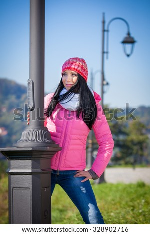 Young woman posing outdoor in autumn. Fashion portrait of pretty girl in cold weather wearing a pink hat and jacket. - stock photo