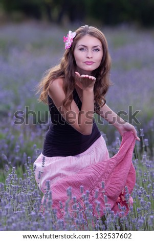 Young woman posing outdoors. Attractive girl in the field of blossoming lavender - stock photo