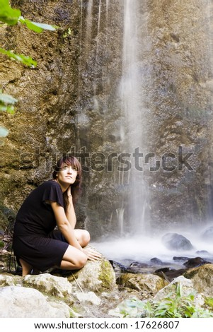 Young woman posing under long exposed waterfall
