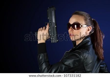 Young woman posing with gun in sunglass - stock photo