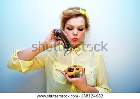 Young woman pouring chocolate sauce over chocolate chip cookie - stock photo