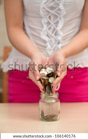 Young woman pouring coins into a jar - stock photo