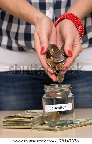 Young woman pouring coins into a jar. She is saving money for better education. - stock photo