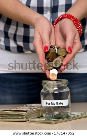 Young woman pouring coins into a jar. She is saving money for her baby. - stock photo