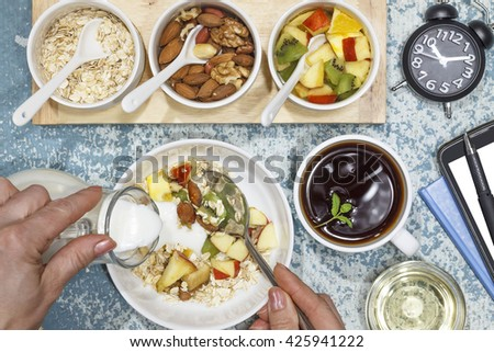 Young woman pouring cream or yogurt  in a bowl with fruit salad , notebook. Proper nutrition, diet - stock photo