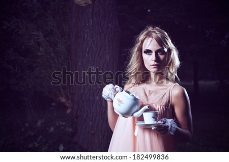 Young Woman Pouring Tea Wearing Vintage Dress Outdoors