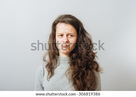 Young woman pouted, hurt. On a gray background. - stock photo