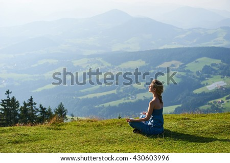 Young woman practice yoga on mountain peak - stock photo