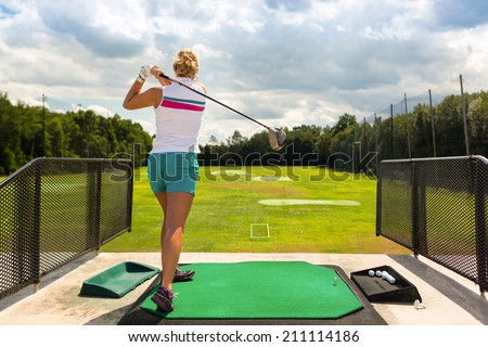 Young woman practices her golf swing on driving range, view from behind - stock photo