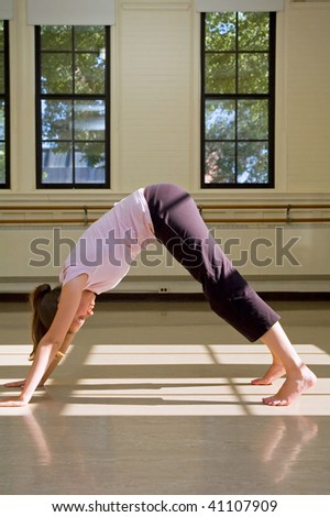 Young woman practicing downward-looking dog pose on floor. - stock photo