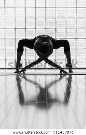 Young woman practicing in a yoga studio. Artistic shot showing reflection and lines. - stock photo