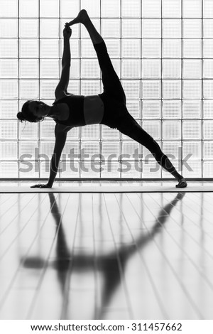 Young woman practicing in a yoga studio. This is an advanced version of side plank pose or vasisthasana - stock photo