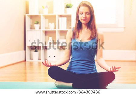 Young woman practicing meditation at home - stock photo