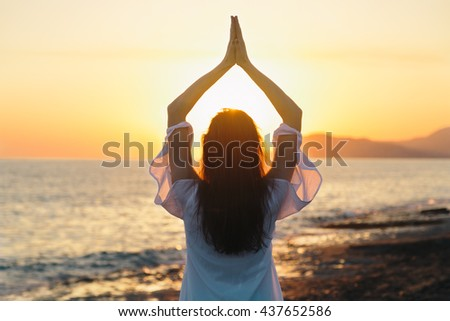 Young woman practicing morning yoga in nature at the beach. Health lifestyle concept. Toned image. Copy space text.
