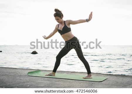 Young woman practicing yoga at  seashore at sunrise or sunset