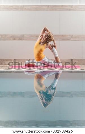 Young woman practicing yoga at swimming pool, Eka pada Rajakapotasana / Pigeon pose  - stock photo
