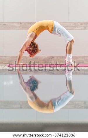Young woman practicing yoga at swimming pool, Urdhva Dhanurasana / Bridge pose - stock photo