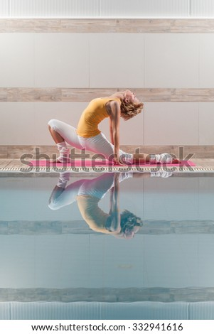 Young woman practicing yoga at swimming pool, Virabhadrasana - Variation of Warrior pose - stock photo