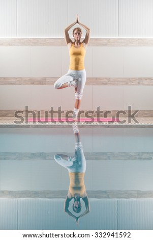 Young woman practicing yoga at swimming pool, Vrikshasana / Tree pose - stock photo