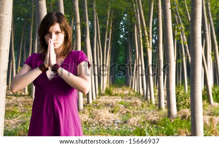 Young woman practicing yoga in a forest.
