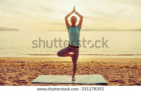 Young woman practicing yoga in pose of tree on beach near the sea at sunset in summer, front view