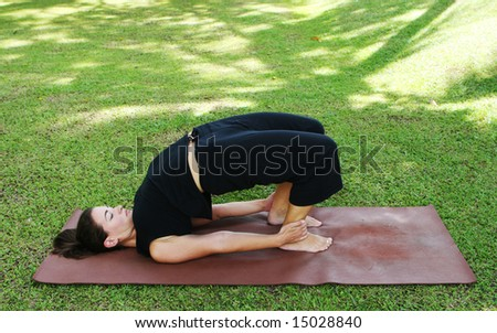 Young woman practicing yoga in the park. - stock photo