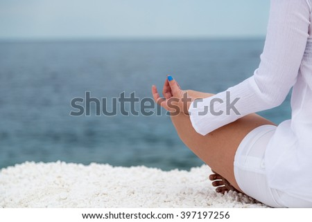 Young woman practicing yoga near marble beach on Thassos island, Greece. - stock photo