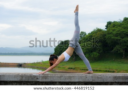 Young woman practicing yoga on the barrier of reservoir.