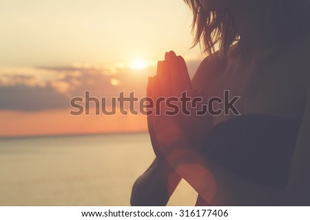 Young woman practicing yoga on the beach. - stock photo