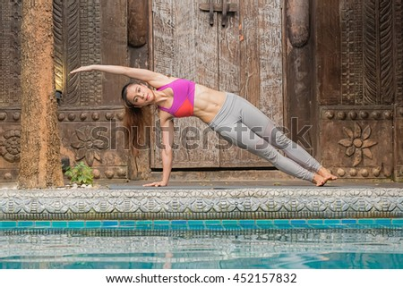 Young woman practicing yoga on the pool.