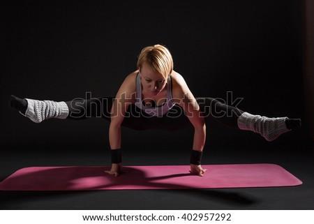 Young woman practicing yoga, Tittibhasana / Insect / Firefly Pose - stock photo