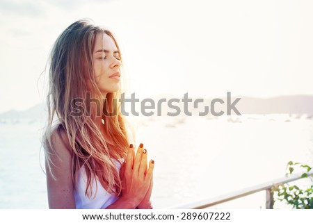 Young Woman Practicing Yoga with the Put Hands Before a Breast. Beach Sunset - stock photo