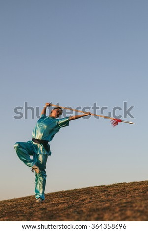 Young Woman Practising Wushu at Sunset with a Spear - stock photo