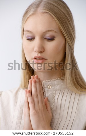 Young woman praying, looking down. - stock photo
