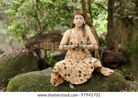 young woman praying meditation in wild nature, thailand - stock photo