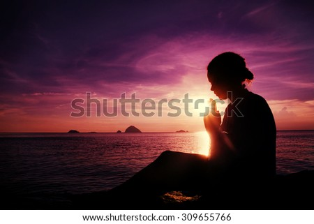 Young Woman Praying Sunset Over Ocean Concept