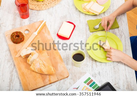 Young woman preparing breakfast while getting online information about nutrition.