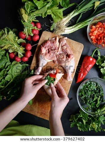 Young woman preparing chicken with vegetables  - stock photo