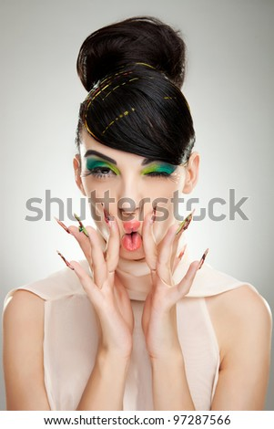 young woman pressing her lips with her fingers on gray studio background - stock photo