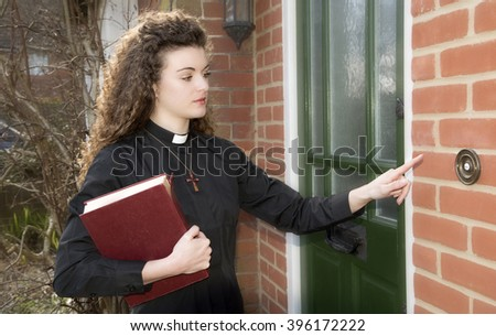 Young woman priest on a house callt ringing door bell of a house - stock photo