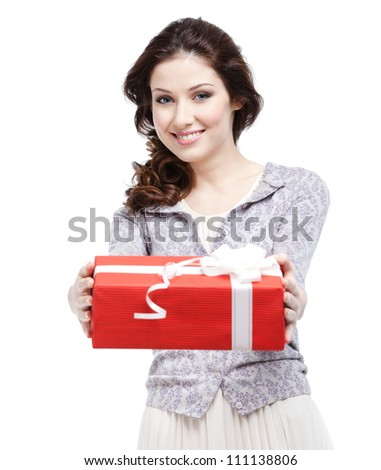 Young woman proffers a gift wrapped in red paper, isolated on white - stock photo