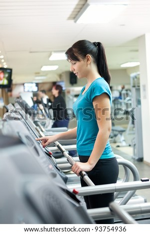 young woman programming running machine in gym - stock photo