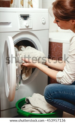 Young woman pulls clean laundry from the washing machine