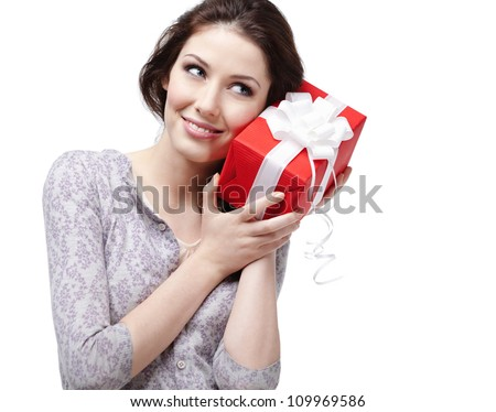 Young woman puts her ear to the present wrapped in red paper, isolated on white - stock photo