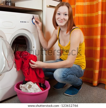 Young woman putting clothes into washing machine and smiling