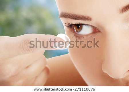 Young woman putting contact lens. - stock photo
