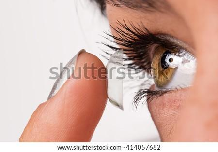 Young woman putting contact lens in her eye. Macro shot. - stock photo